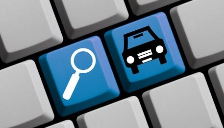 Tastatur mit zwei Buttons, Lupe und Auto als Symbol für die Gebrauchtwagenbewertung.
