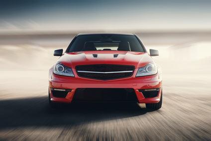 Ein rotes Auto fährt auf die Kamera zu