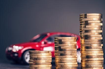 Ein Spielzeugauto steht vor einem Haufen Münzen.